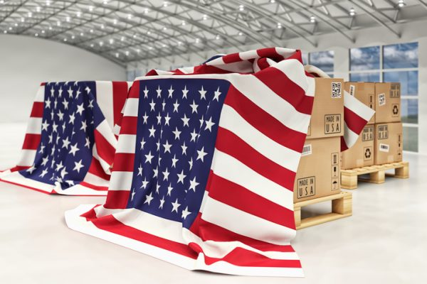 Distribution warehouse with cardboard boxes on pallets covered with USA flags
