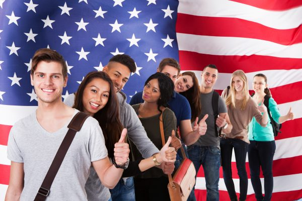Group Of Diverse Students Standing In Front Of American Flag Showing Thumb Up