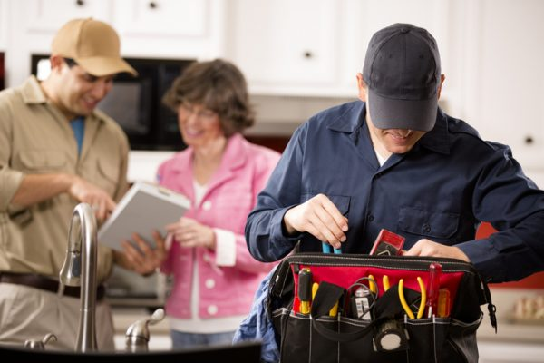 Caucasian and Hispanic repairmen or blue collar/service industry workers make service/house call at customer's home kitchen. Man in foreground looks through his tool box filled with work tools. Other worker holds a clipboard and talks with customer background. Inspector, exterminator, electrician, plumber, repairmen.