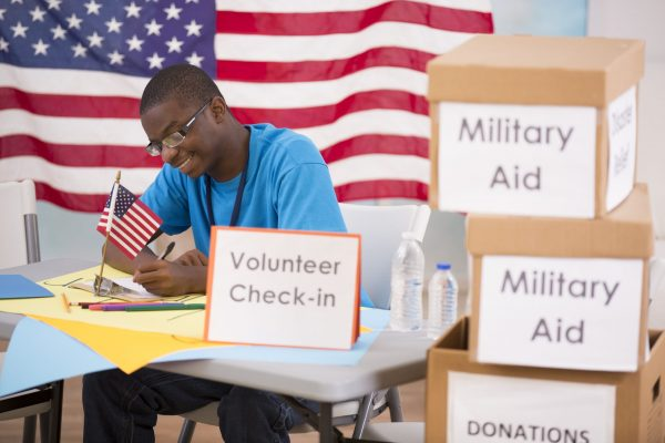 African descent teenage boy signs up as a volunteer to help with a military aid/relief efforts event.  American flag background.