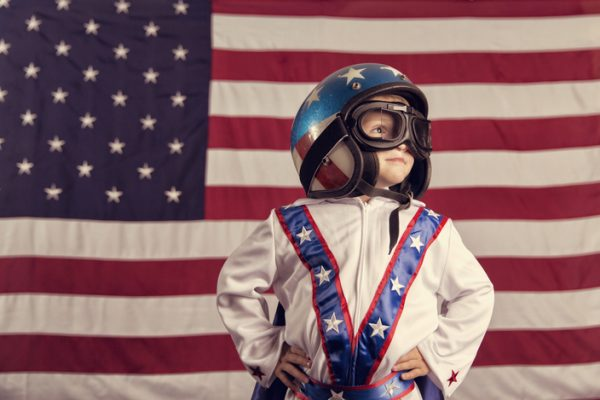 A young boy dressed like a daredevil wears a white jumpsuit, cape and helmet, standing in front of a giant American flag. His hands are on his hips and the boy has a confident  expression.
