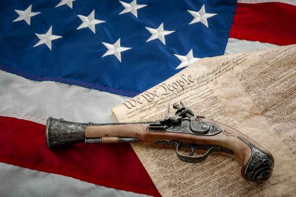 American flag, US constitution and a musket type pistol or a flint (flintlock), which was the type of handgun used at the time of the signing of the constitution